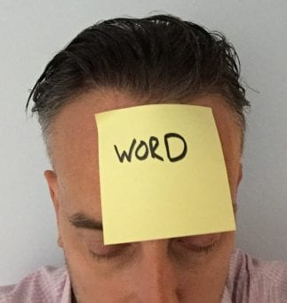 Post-it note with word written on it on a man's head