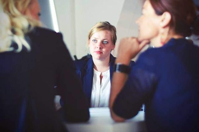 Woman observing two women talking
