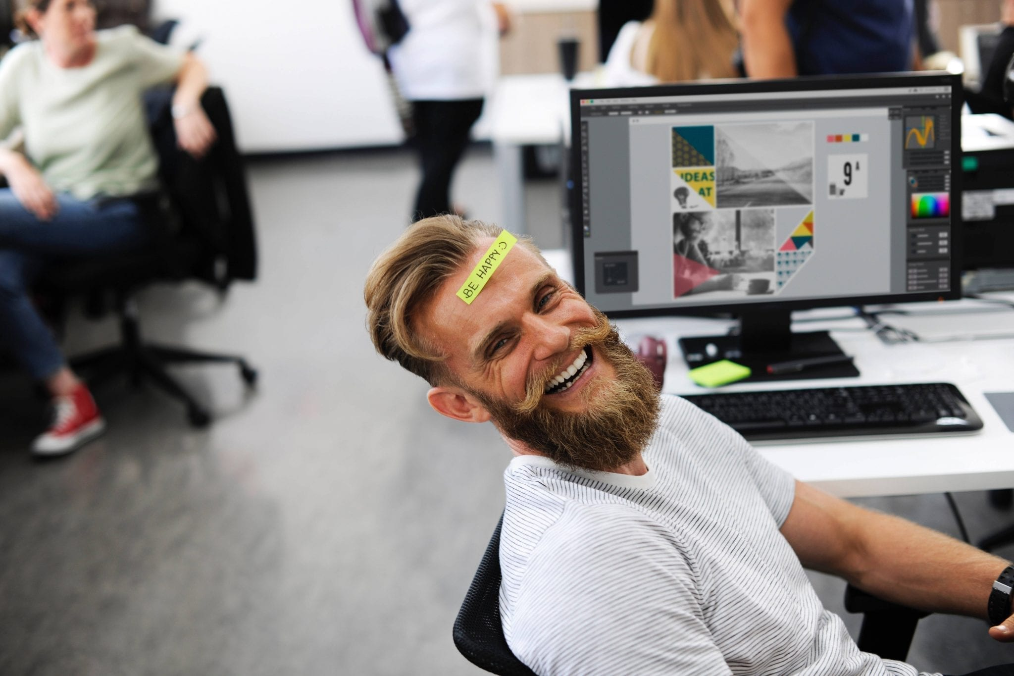 Man laying back on his desk, smiling, a post-it note on his head that says Be Happy