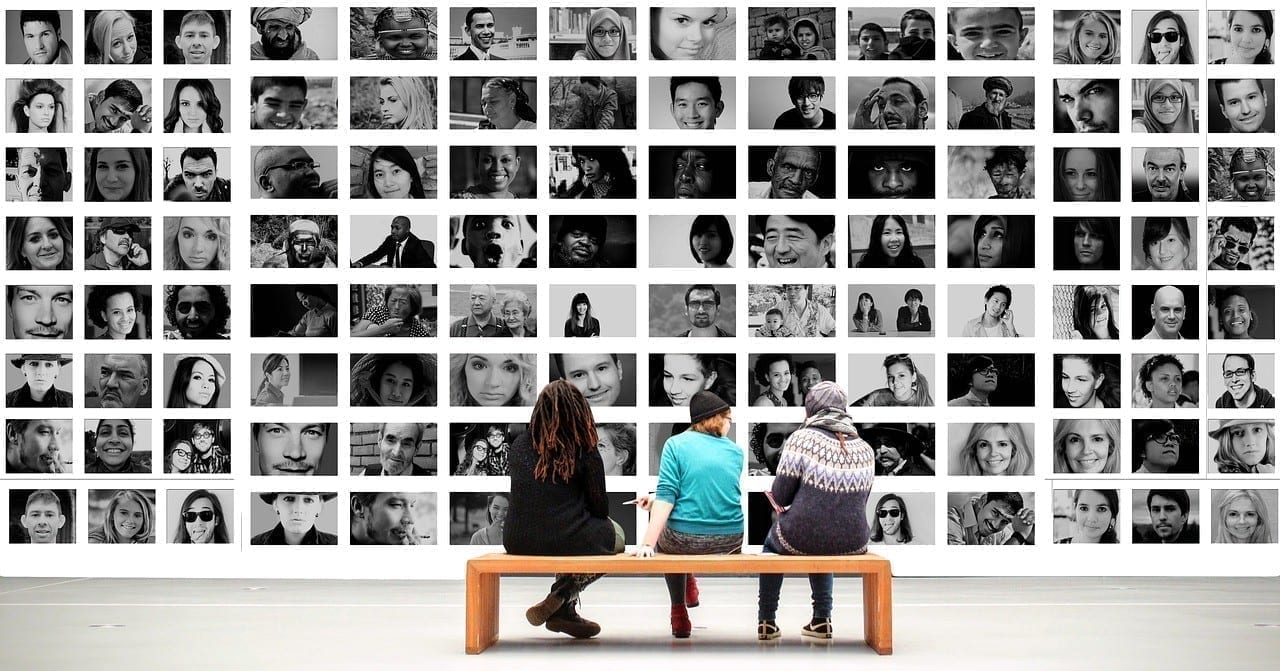 Three people on bench looking at a picture wall of diverse faces