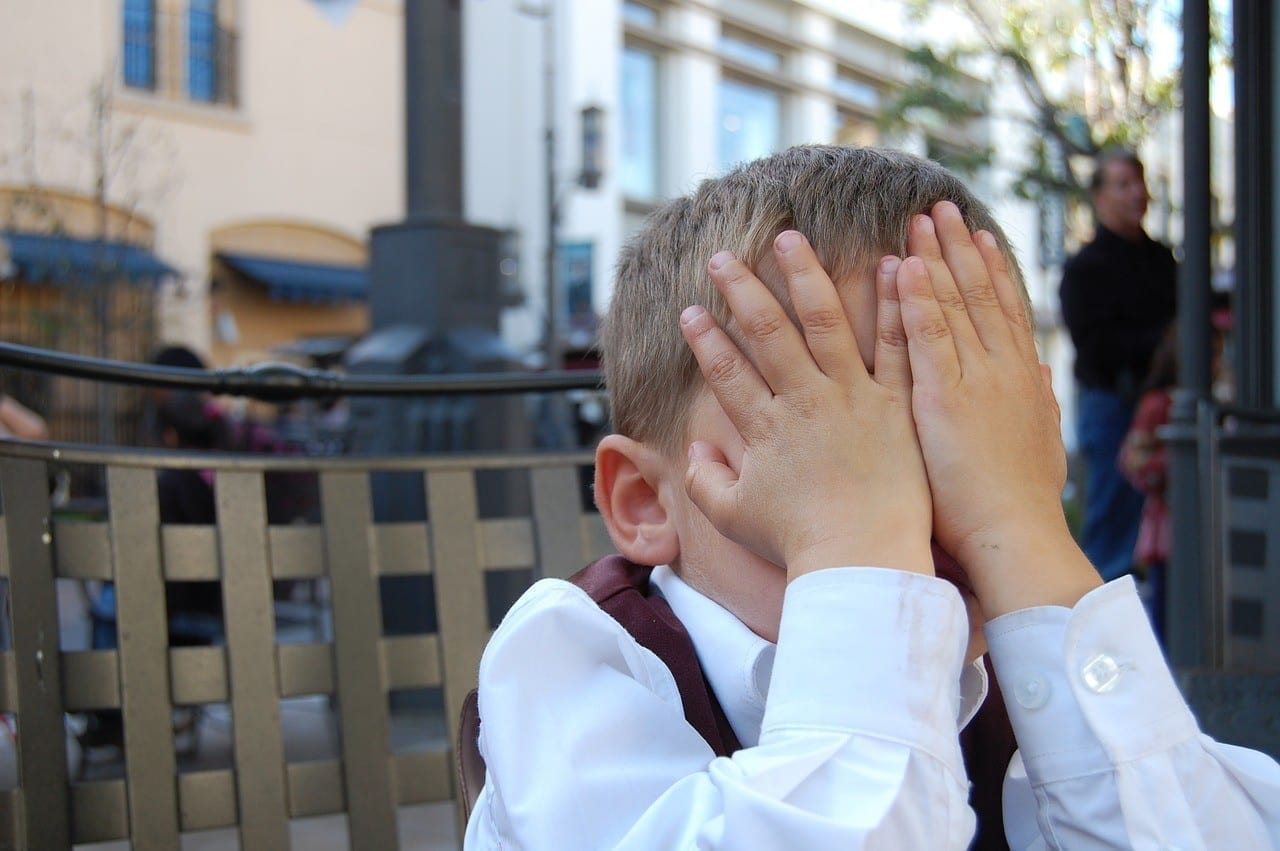 an embarrassed child with hands on face