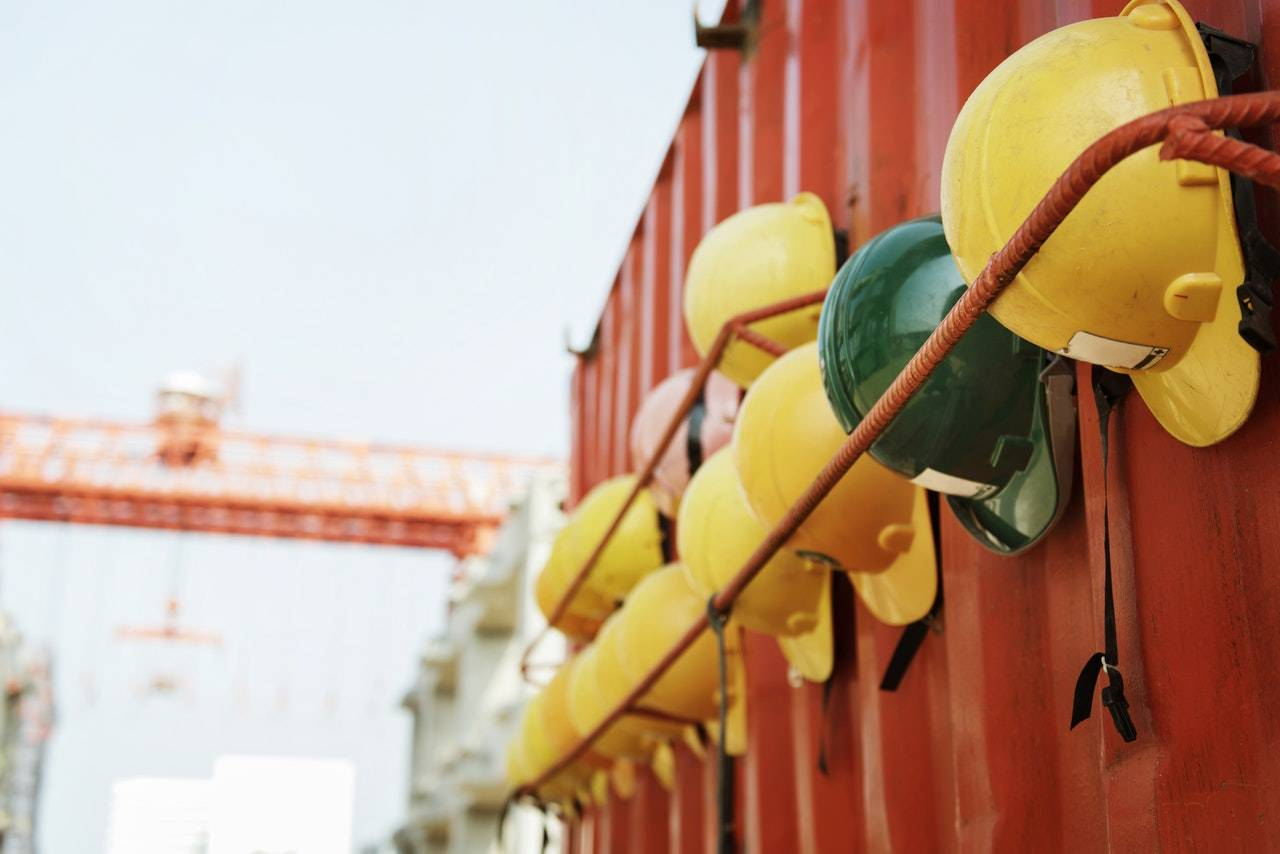Hard hats hanging from the side of a container.