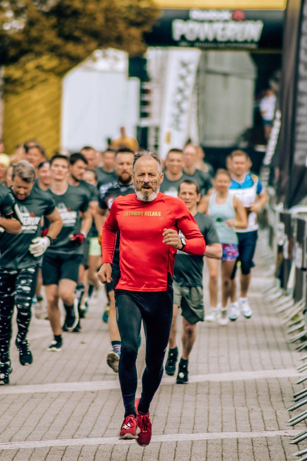 Older man running a marathon among other runners