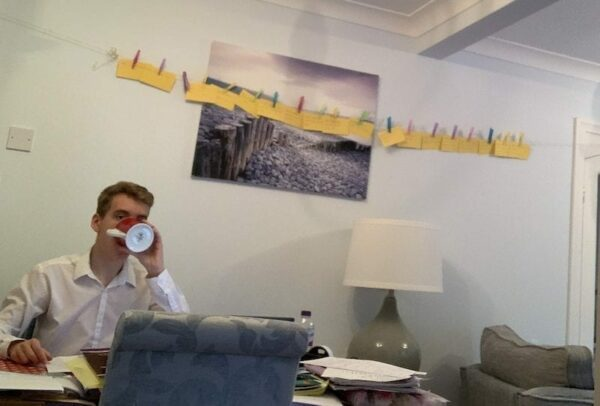 Man drinking from a cup in his office