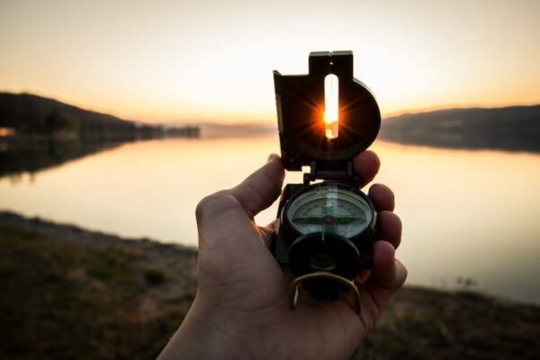 Man holding a compass in front of a lake on a sunset