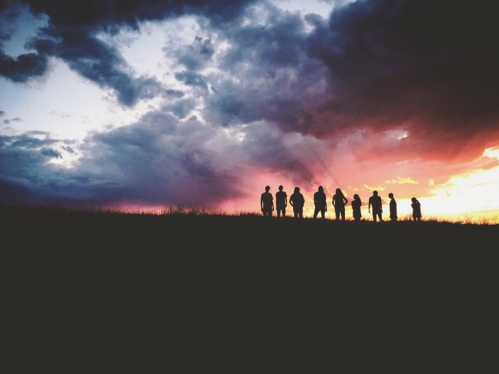 Silhouette of nine people standing in a field watching the sunset