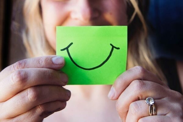 Woman holding a sticky note of a cartoon smiling mouth in front of her face