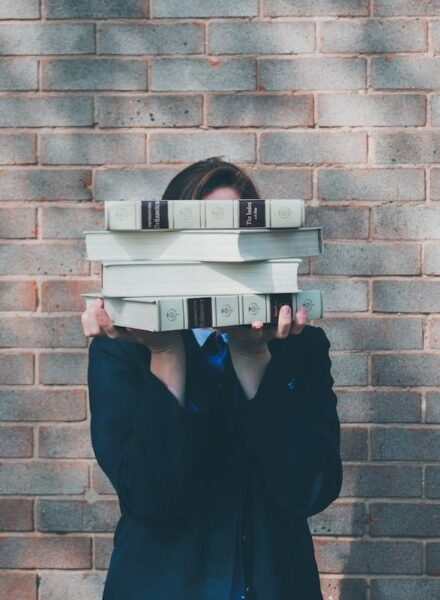 Lady in black holding 4 thick books with her both hands, covering her face