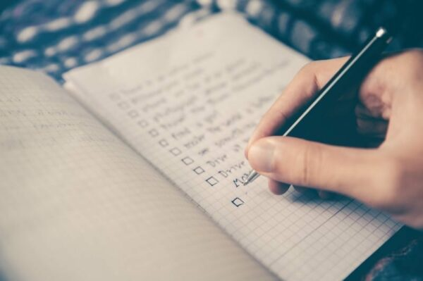 man's hand jotting down notes on a notebook