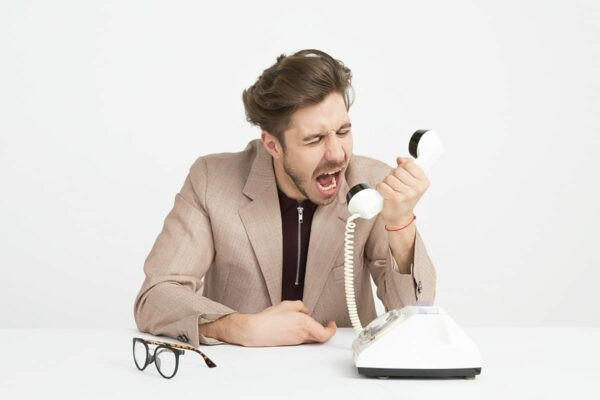 Businessman shouting into a white telephone