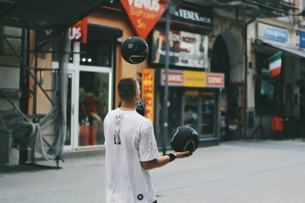 Man juggling three black balls in the middle of the street