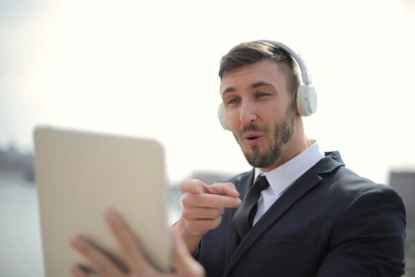 Man in an office attire with his headphones on pointing at his tablet