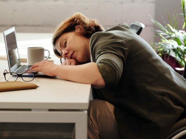 Woman asleep at her desk with her laptop, coffee and glasses in front of her