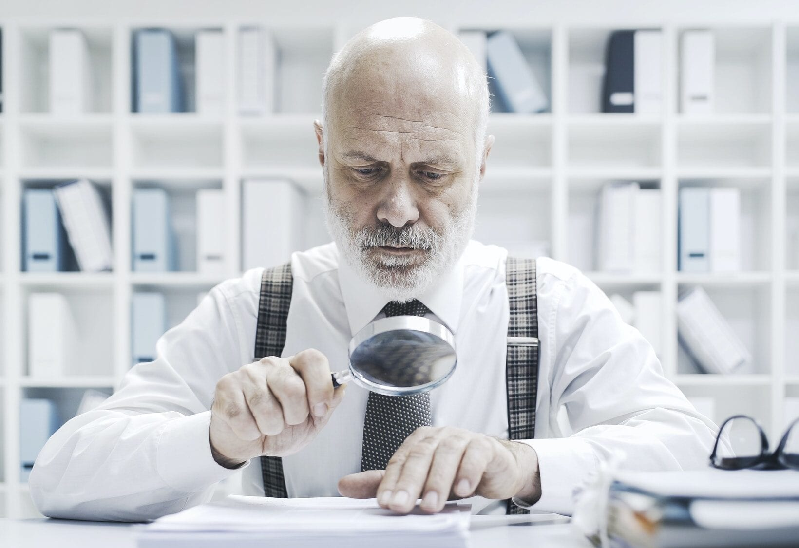 Corporate businessman checking paperwork with a magnifier, Written Communication