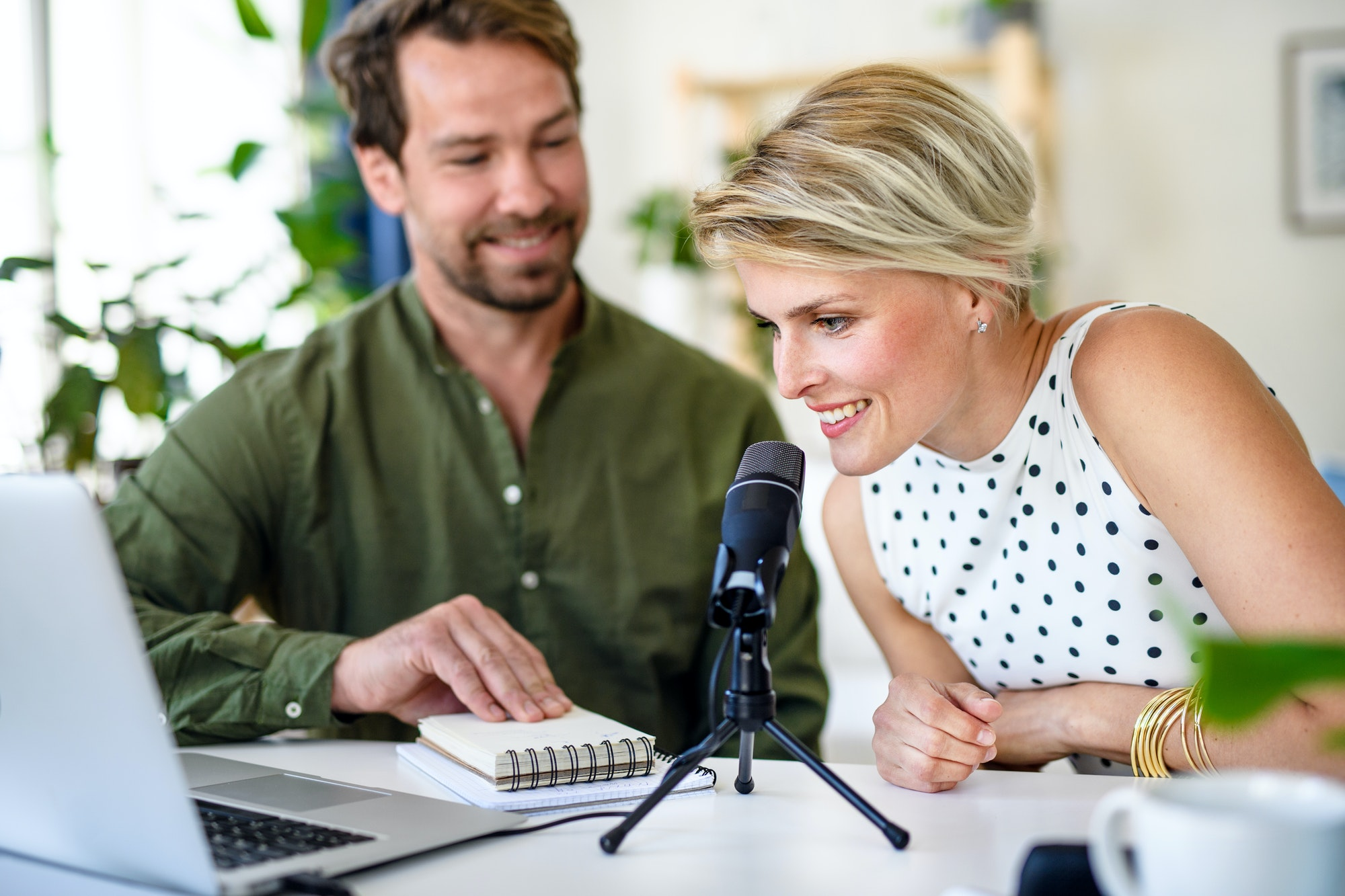 Happy couple with microphone having video call on laptop indoors at home, Podcast